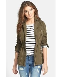 Pairing green skinny jeans with an anorak coat is a comfortable option for running errands in the city.