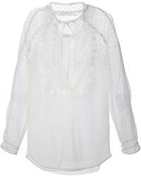 Pair a white duster coat with a long sleeve blouse for a standout ensemble.