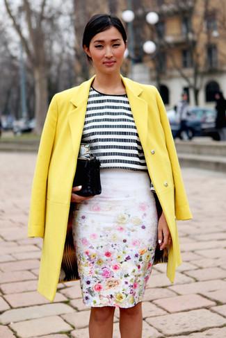 Cómo combinar: abrigo amarillo, camiseta de manga larga de rayas horizontales en blanco y negro, falda lápiz con print de flores blanca, cartera sobre de ante negra