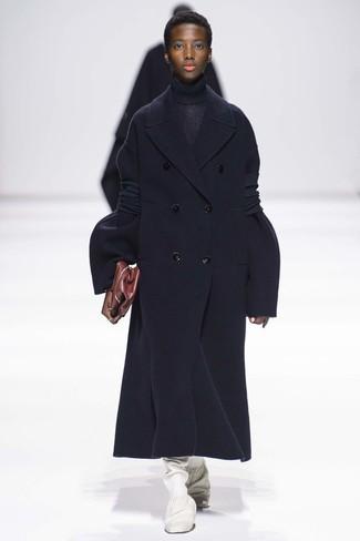 Cómo combinar: abrigo azul marino, jersey de cuello alto de punto azul marino, botas de caña alta de cuero blancas, cartera sobre de cuero burdeos