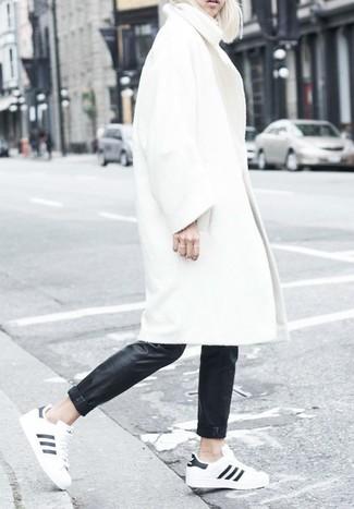 Cómo combinar: abrigo blanco, pantalones pitillo de cuero negros, tenis en blanco y negro