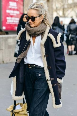 Cómo combinar: abrigo azul marino, blusa de manga larga de lino blanca, pantalones anchos vaqueros azul marino, mochila con cordón de ante amarilla