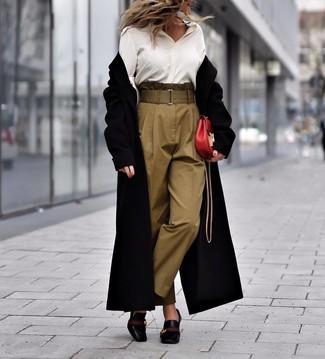 Cómo combinar: abrigo negro, camisa de vestir de seda blanca, pantalón de pinzas verde oliva, zapatos de tacón de cuero negros