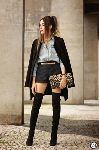 Cómo combinar: abrigo negro, camisa vaquera celeste, pantalones cortos negros, botas sobre la rodilla de ante negras