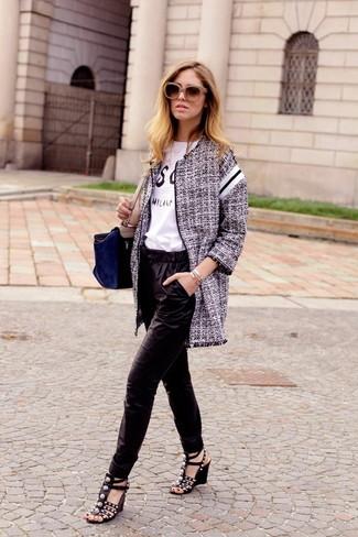 Cómo combinar: abrigo de tweed gris, camiseta con cuello circular estampada en blanco y negro, pantalón de pinzas de seda negro, sandalias con cuña de cuero con tachuelas negras