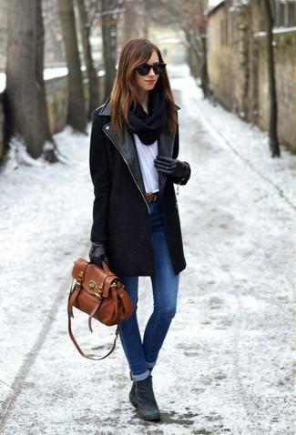 Elige un abrigo negro y unos vaqueros pitillo azules para conseguir una apariencia relajada pero chic. Este atuendo se complementa perfectamente con botines de ante gris oscuro.