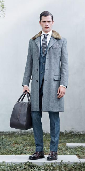 Cómo combinar: abrigo con cuello de piel de espiguilla gris, traje de lana de rayas verticales azul, camisa de vestir blanca, zapatos con doble hebilla de cuero en marrón oscuro