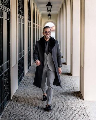Cómo combinar: abrigo con cuello de piel negro, traje gris, camisa de vestir negra, mocasín con borlas de ante negro