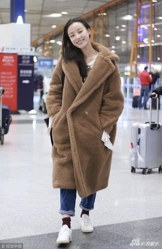 Cómo combinar: abrigo de piel marrón claro, blusa de manga larga blanca, vaqueros azules, tenis de cuero blancos