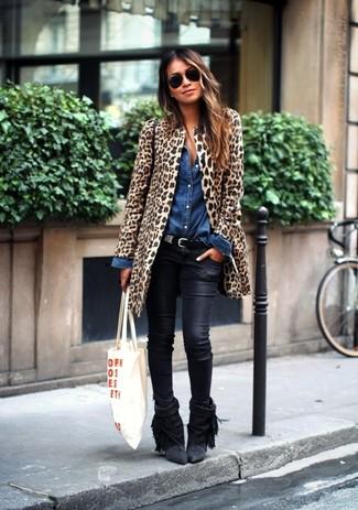 Cómo combinar: abrigo de piel de leopardo marrón claro, camisa vaquera azul, vaqueros pitillo de cuero negros, botines de ante сon flecos negros