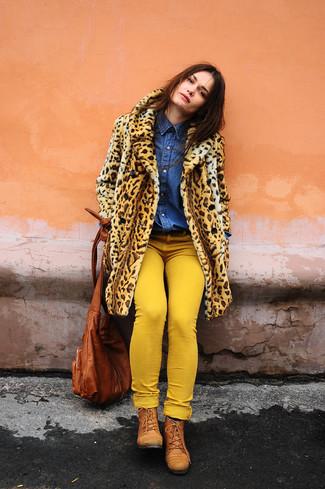 Cómo combinar: abrigo de piel de leopardo marrón claro, camisa vaquera azul, vaqueros pitillo amarillos, botas planas con cordones de cuero en tabaco