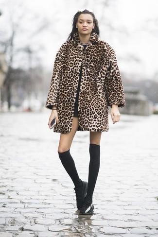 Cómo combinar: abrigo de piel de leopardo marrón claro, camiseta con cuello circular negra, pantalones cortos negros, tenis de cuero negros