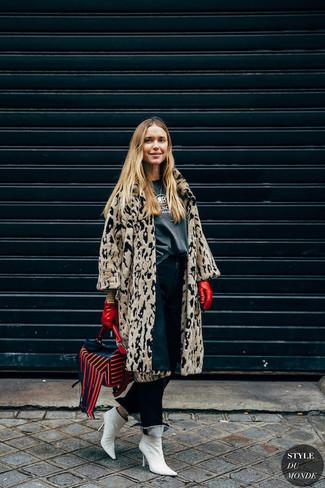 Cómo combinar: abrigo de piel de leopardo en beige, camiseta con cuello circular estampada en gris oscuro, vaqueros azul marino, botines de cuero blancos