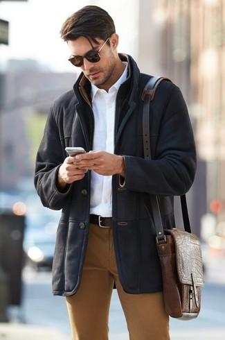Cómo combinar: abrigo de piel de oveja negro, camisa de vestir blanca, pantalón chino en tabaco, bolso mensajero de cuero marrón