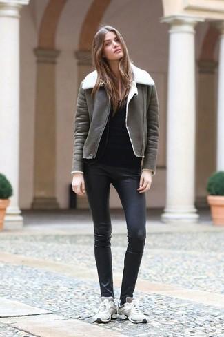 Cómo combinar: abrigo de piel de oveja en gris oscuro, camiseta de manga larga negra, pantalones pitillo de cuero negros, tenis blancos
