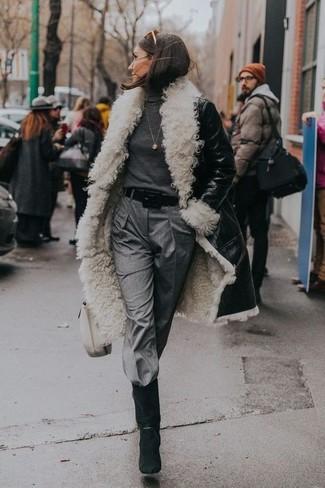 Cómo combinar: abrigo de piel de oveja en negro y blanco, jersey de cuello alto en gris oscuro, pantalón de pinzas gris, botas a media pierna de ante negras