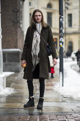 Cómo combinar: abrigo de piel de oveja verde oliva, jersey de cuello alto blanco, pantalones pitillo de cuero negros, botas planas con cordones de cuero negras