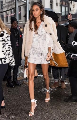 Cómo combinar: abrigo de piel en beige, vestido recto con print de flores blanco, sandalias de tacón de cuero blancas, bolso de hombre de cuero marrón claro