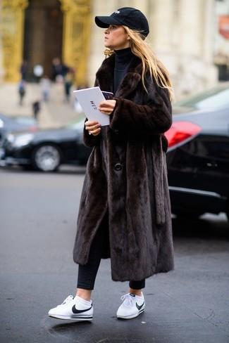 Empareja un abrigo de piel marrón oscuro con una gorra inglesa negra y te verás impresionante en cualquier lugar y en cualquier momento. Haz este look más informal con tenis de cuero blancos.