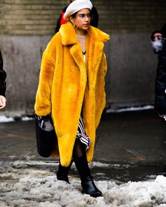 Cómo combinar: abrigo de piel amarillo, vestido midi de rayas verticales en blanco y negro, botines de cuero con print de serpiente negros, bolsa tote de cuero negra