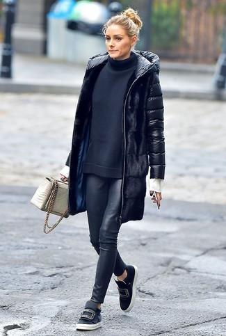 Cómo combinar: abrigo de plumón negro, jersey de cuello alto negro, leggings de cuero negros, zapatillas slip-on de cuero con adornos negras
