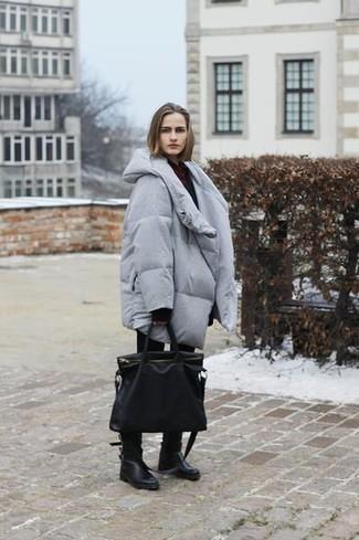 Cómo combinar: abrigo de plumón gris, jersey oversized negro, vaqueros pitillo negros, botas a media pierna de cuero negras