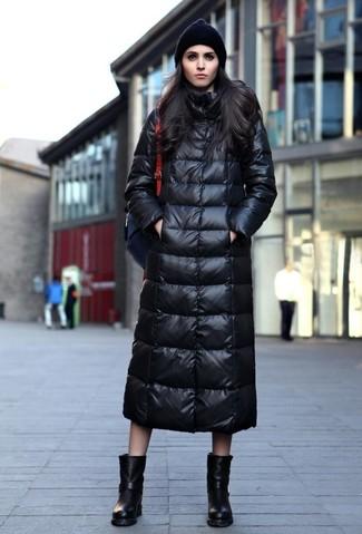 Cómo combinar: abrigo de plumón negro, botas a media pierna de cuero negras, mochila de cuero negra, gorro negro