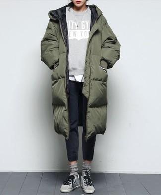 Cómo combinar: abrigo de plumón verde oliva, sudadera estampada gris, camiseta con cuello circular blanca, pantalón de chándal negro