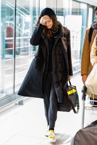 Cómo combinar: abrigo de plumón negro, sudadera con capucha negra, pantalón de chándal en gris oscuro, tenis de lona amarillos