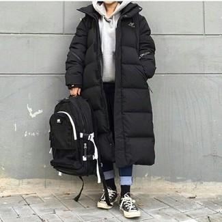 Cómo combinar: abrigo de plumón negro, sudadera con capucha gris, vaqueros azul marino, tenis de lona en negro y blanco