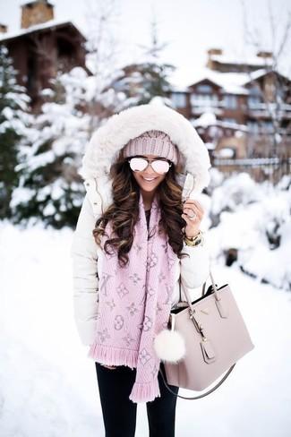 Cómo combinar: abrigo de plumón blanco, vaqueros pitillo negros, bolsa tote de cuero rosada, gorro de punto rosado