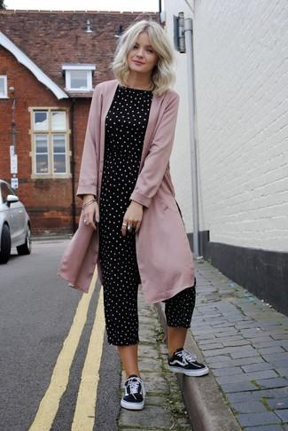 Cómo combinar: abrigo duster rosado, mono a lunares en negro y blanco, tenis de lona en negro y blanco