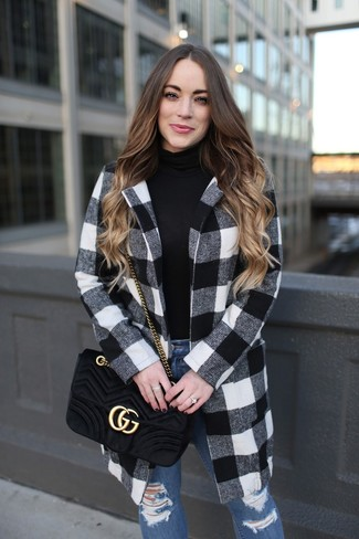 Cómo combinar: abrigo de cuadro vichy en blanco y negro, jersey de cuello alto negro, vaqueros pitillo desgastados azules, bolso bandolera de ante acolchado negro