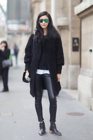 Cómo combinar: abrigo con relieve negro, jersey con cuello circular con relieve negro, camiseta con cuello circular blanca, pantalones pitillo de cuero negros
