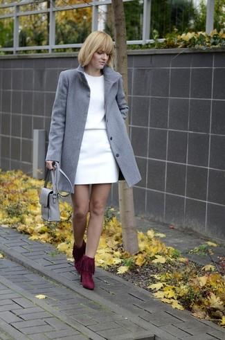 Cómo combinar: abrigo gris, jersey con cuello circular blanco, minifalda blanca, botines de ante сon flecos burdeos