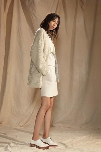 Cómo combinar: abrigo de forro polar en beige, jersey con cuello circular blanco, minifalda de punto blanca, zapatos oxford de cuero blancos