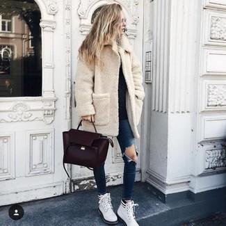 Cómo combinar: abrigo de forro polar en beige, jersey con cuello circular negro, vaqueros pitillo desgastados azul marino, botas planas con cordones de cuero blancas