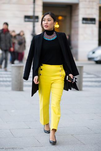 Cómo combinar: abrigo negro, jersey de cuello alto negro, pantalones pitillo amarillos, zapatos de tacón de cuero negros
