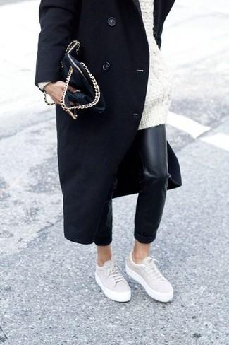 Cómo combinar: abrigo negro, jersey oversized de punto blanco, pantalones pitillo de cuero negros, tenis en beige