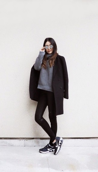 Cómo combinar: abrigo negro, jersey oversized de punto gris, vaqueros pitillo de cuero negros, deportivas en negro y blanco