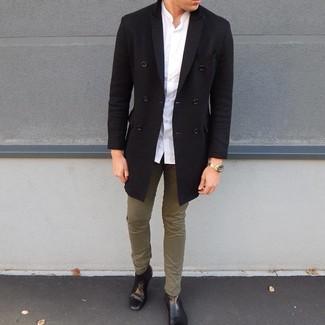 Cómo combinar: abrigo largo negro, camisa de manga larga blanca, pantalón chino verde oliva, botines chelsea de cuero negros