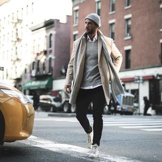 Cómo combinar: abrigo largo en beige, camisa de manga larga blanca, vaqueros negros, zapatillas altas de cuero blancas