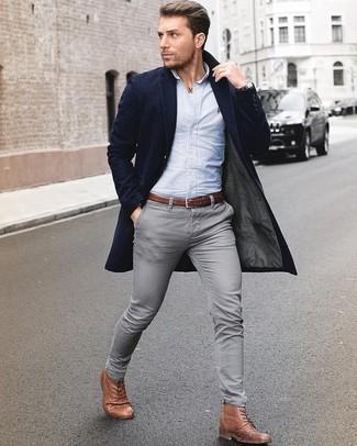 Cómo combinar: abrigo largo azul marino, camisa de vestir celeste, vaqueros pitillo grises, botas formales de cuero marrónes