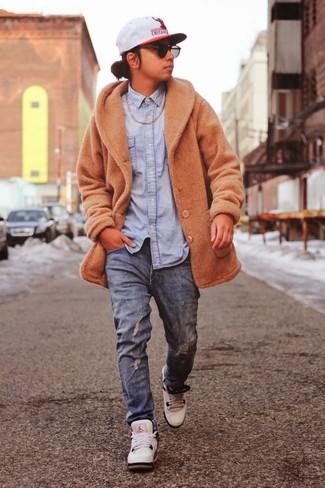 Cómo combinar: abrigo largo marrón claro, camisa vaquera celeste, vaqueros azules, deportivas blancas