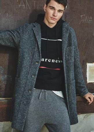 Cómo combinar: abrigo largo en gris oscuro, sudadera con capucha estampada en negro y blanco, camiseta con cuello circular blanca, pantalón de chándal gris