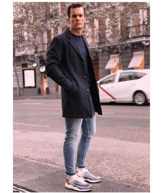 Cómo combinar: abrigo largo negro, jersey con cuello circular azul marino, vaqueros pitillo desgastados celestes, deportivas en blanco y azul marino
