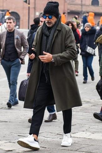 Cómo combinar: abrigo largo en gris oscuro, jersey de cuello alto negro, pantalón chino negro, tenis de cuero blancos