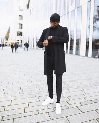 Cómo combinar: abrigo largo negro, jersey de cuello alto negro, pantalón chino negro, tenis de cuero blancos