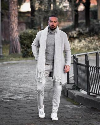 Cómo combinar: abrigo largo gris, jersey de cuello alto de lana gris, pantalón chino gris, tenis de cuero blancos