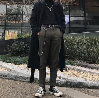 Cómo combinar: abrigo largo negro, jersey de cuello alto negro, pantalón de vestir verde oliva, tenis de lona en negro y blanco